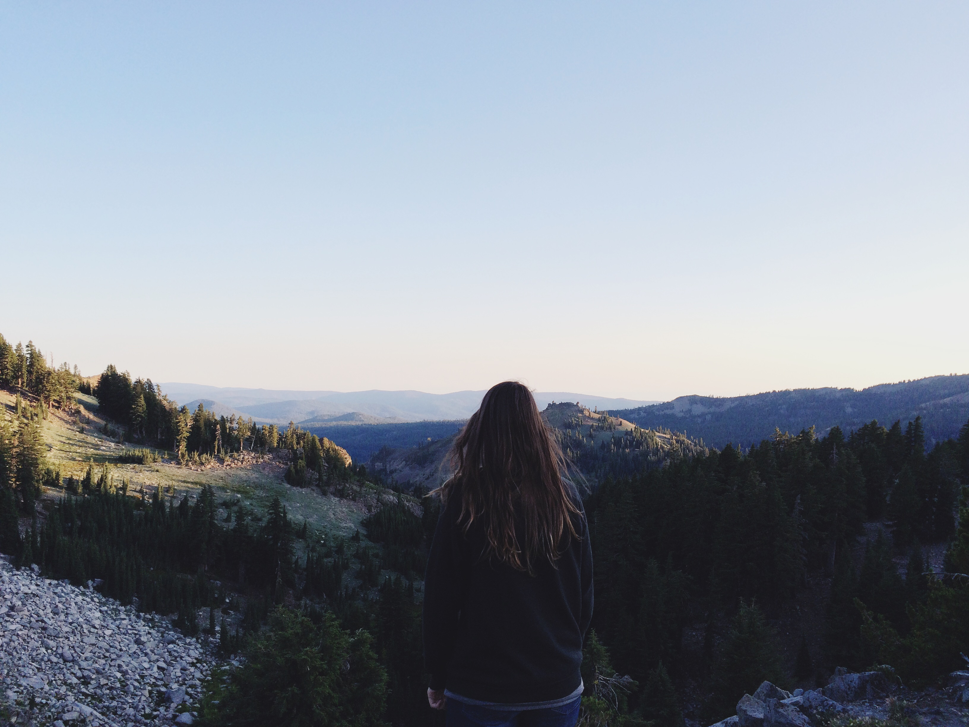 girl standing on cliff- overlooking mountain