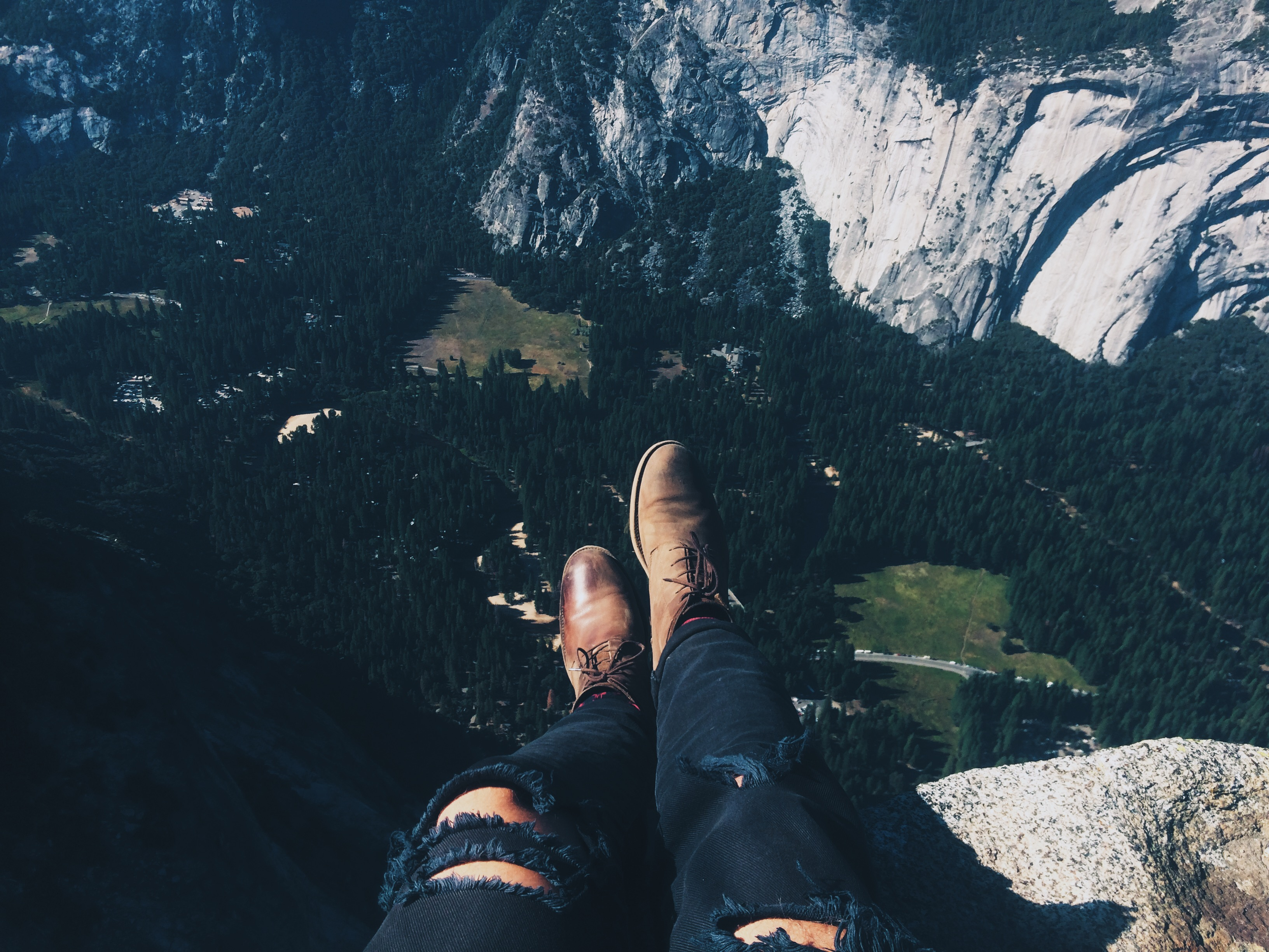 torn jeans and boots sitting on cliff